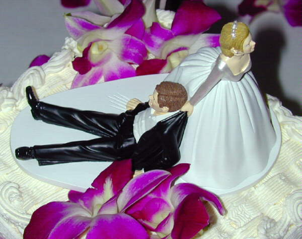 Decoration atop a wedding cake, showing the groom being dragged to the altar (or perhaps home afterwards to wash the dishes).